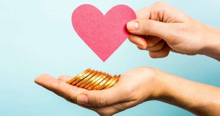 Two hands holding a red heart and money as a symbol of Facebook Donate